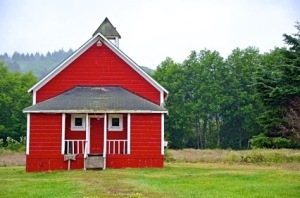 Little red schoolhouse in meadow on misty morning